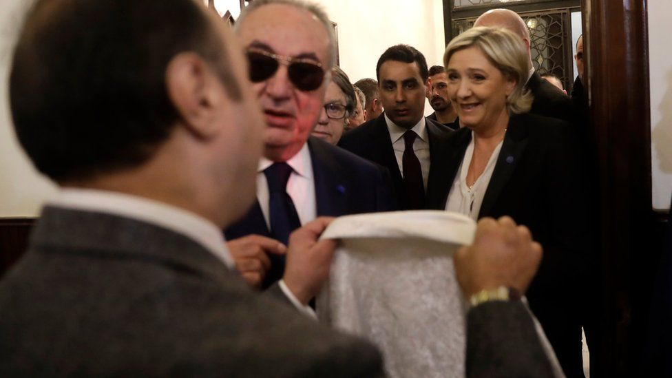 An aide of Lebanon's Grand Mufti Sheikh Abdel-Latif Derian, left, gives a head scarf to French far-right presidential candidate Marine Le Pen, right, to wear during her meeting with the Mufti but she refused, upon her arrival at Dar al-Fatwa the headquarters of the Sunni Mufti, in Beirut, Lebanon, Tuesday, 21 Feb, 2017