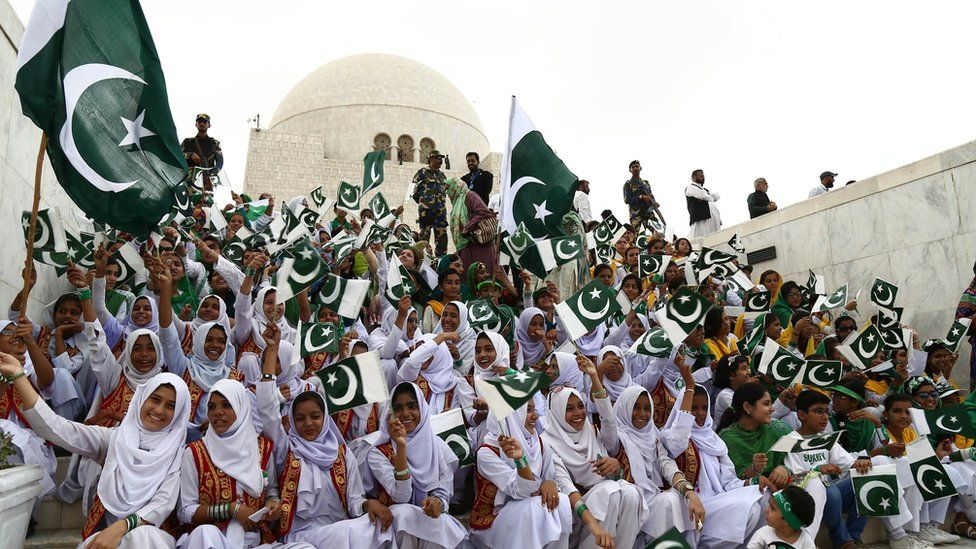 Pakistani students hold national flags during a ceremony at the mausoleum of Pakistan's founder Mohammad Ali Jinnah to mark Independence Day in Karachi on 14 August 2017