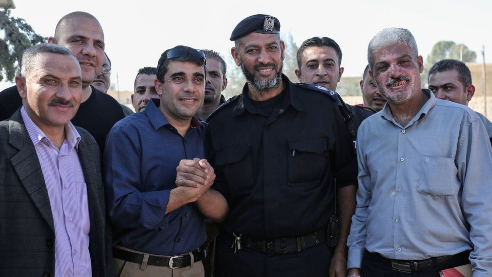 A member of the Palestinian Authority (C-L) shakes hands with Hamas security men at the Rafah border crossing with Egypt (1 November 2017)