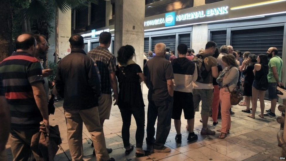 People queue up to withdraw money from an ATM outside a branch of Greece's National Bank in Athens (28 June 2015)