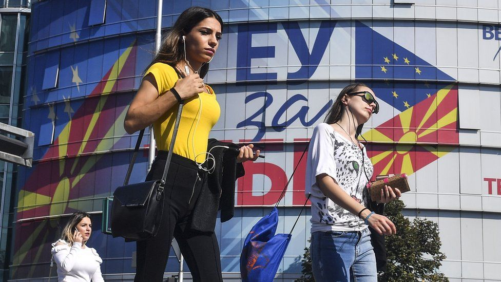 "People walk in front of the offices of the European Union with logos reading ""EU for You"", in Skopje, North Macedonia (18 Oct 2019)"