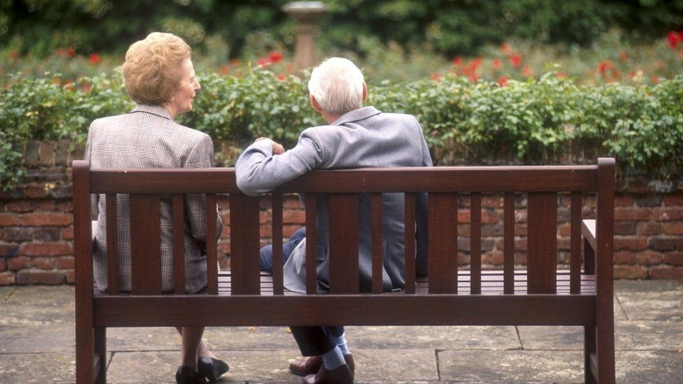 Margaret Thatcher sits on a bench with her husband, Denis at Chequers