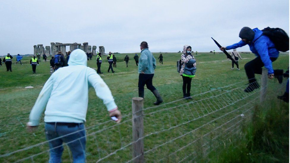 People climb over a fence to get into Stonehenge ancient stone circle during the Summer Solstice celebrations