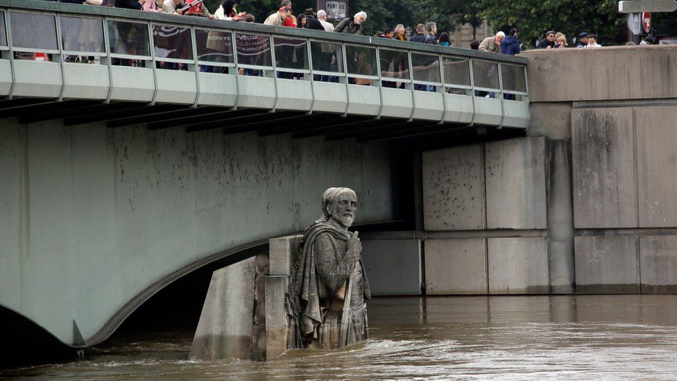People looking at the floods stand on the Alma bridge by the Zouave statue which is used as a measuring instrument during floods in Paris, France Saturday June 4, 2016