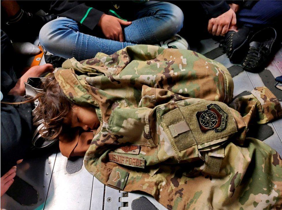 Un niño afgano duerme en el suelo de un avión de la Fuerza Aérea de Estados Unidos durante un vuelo de evacuación desde Kabul