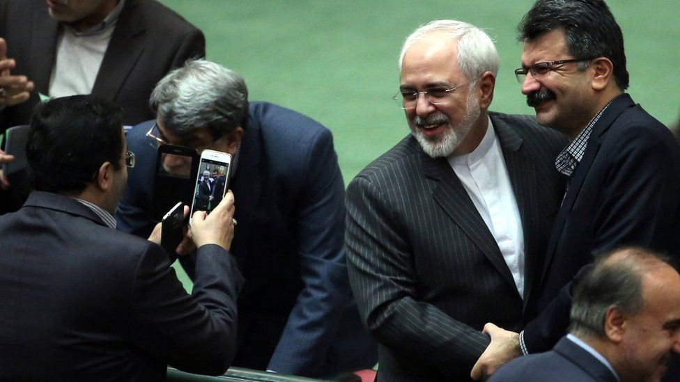 Iranian Foreign Minister Mohammad Javad Zarif is greeted by colleagues on the floor of the Iranian parliament