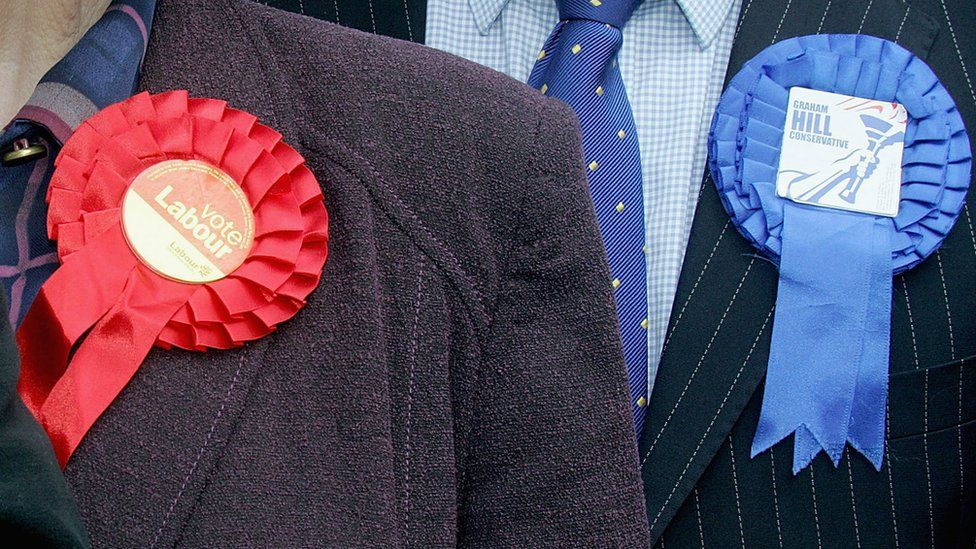 Election candidates wearing Labour and Conservative rosettes