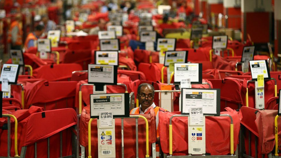 An employee sorts deliveries at a Royal Mail centre in London during the Christmas period
