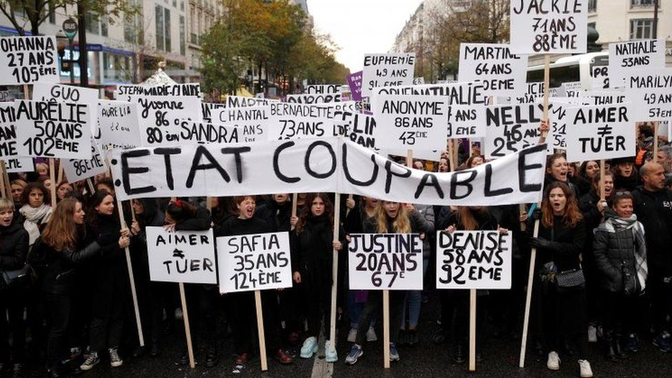 """Protesters in Paris hold slogans that read: """"The state is guilty"""". Photo: 23 November 2019"""