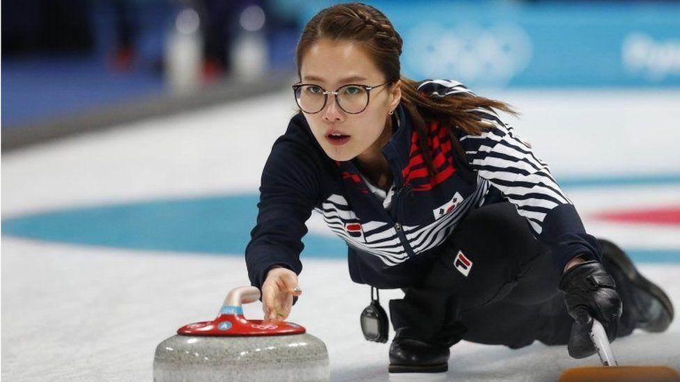 Skip Kim Eun-jung of South Korea delivers a stone.