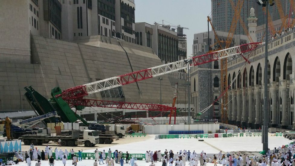 Muslim pilgrims walk past the crane that collapsed at the Grand Mosque in Saudi Arabia's holy Muslim city of Mecca - 12 September 2015