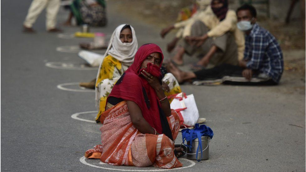 People waiting inside marked spots to maintain social distancing at a food distribution centre