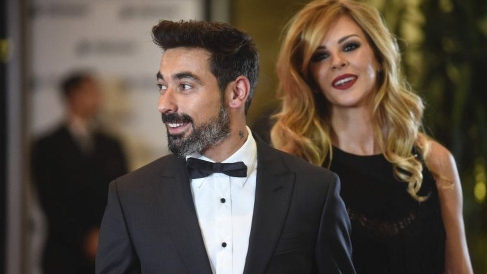 """Argentine footballer Ezequiel Lavezzi and his wife pose on a red carpet upon arrival to attend Argentine football star Lionel Messi and Antonella Roccuzzo""""s wedding in Rosario, Santa Fe province, Argentina on 30 June 2017."""