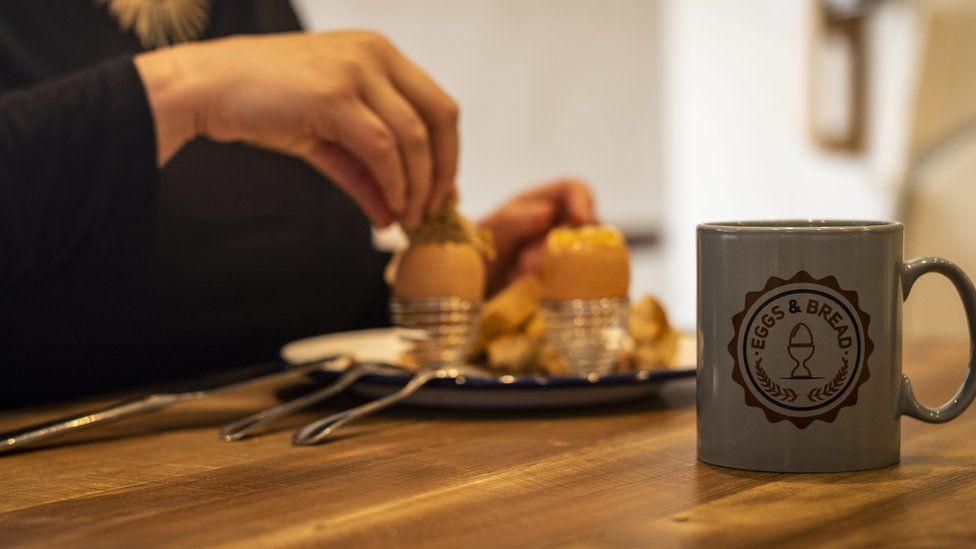A customer enjoys a boiled egg and toast