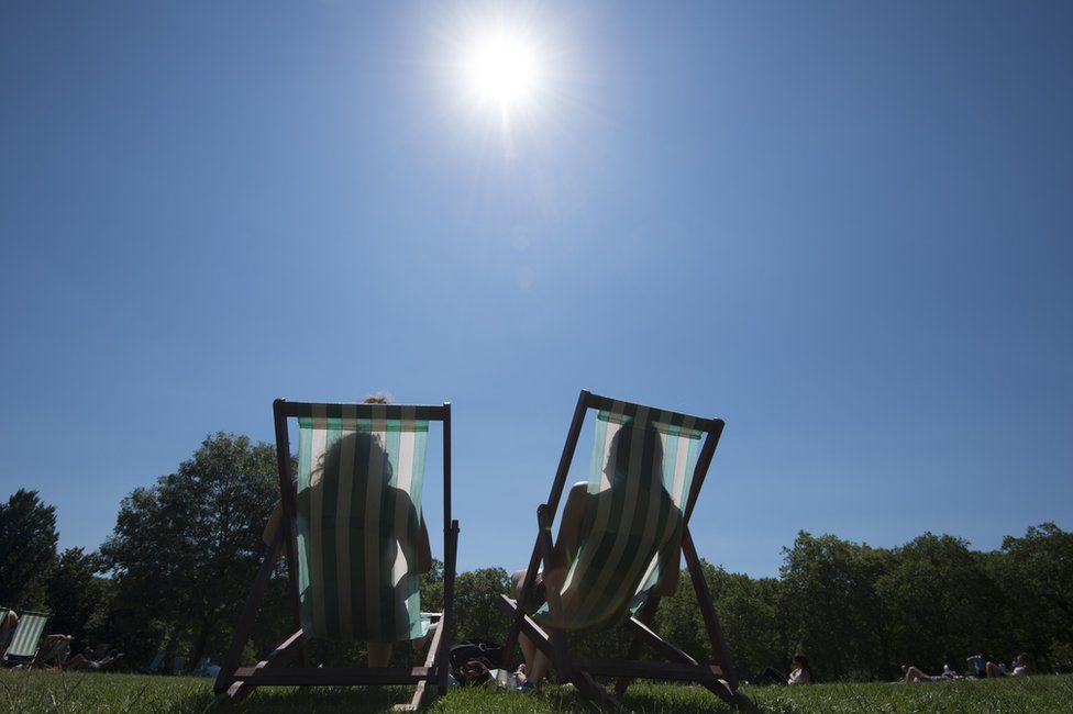 People sitting in deckchairs in the sun
