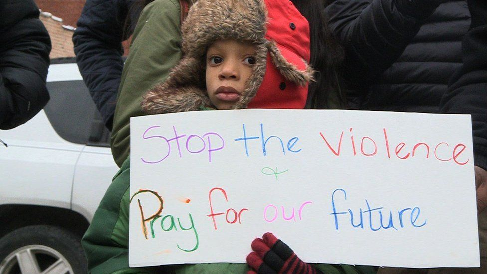 "Child at a demo with a banner that says ""Stop The Violence"""