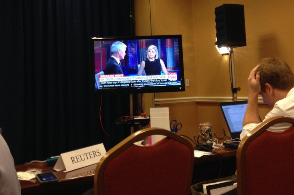 Pool reporters file their copy and watch CNN as the information is relayed to the American public