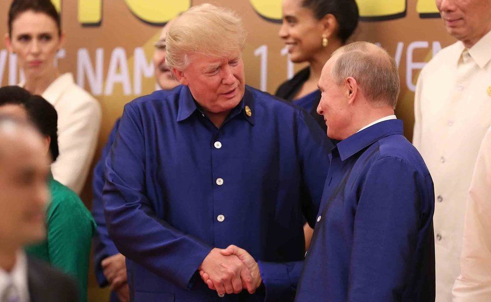 """US President Donald Trump (L) shakes hands with Russia""""s President Vladimir Putin (R) as they pose for a group photo"""