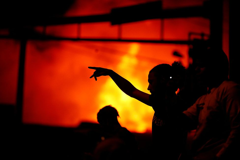 A silhouette of a person pointing as protesters gather to watch a liquor store burning