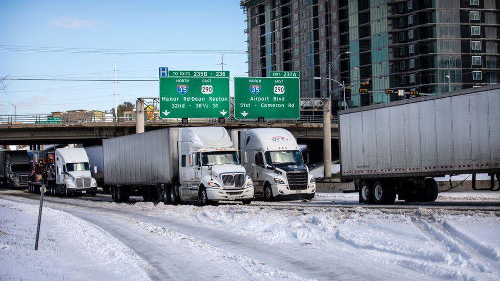 Trucks wait in traffic in Austin, Texas delayed by winter storm Uri