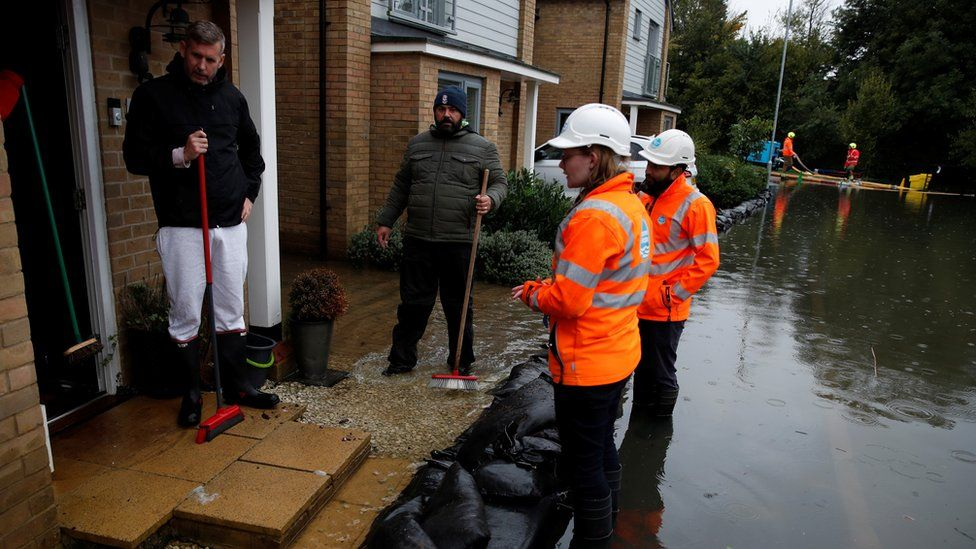 Water utilities workers talk with residents from flooded houses, in Hemel Hempstead, Herts on 4 October 2020