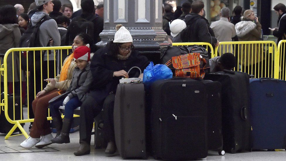 woman and family surrounded by luggage wait in station