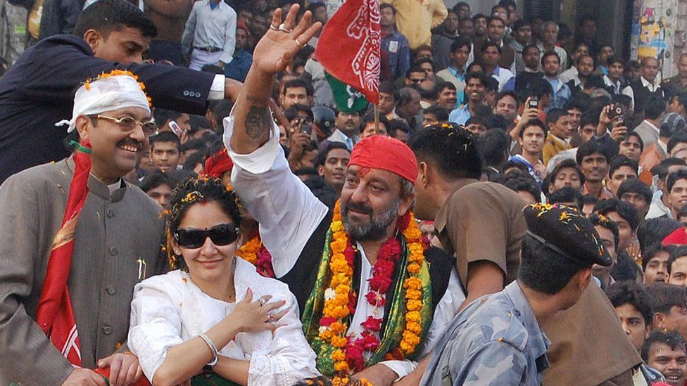 Sanjay Dutt (centre), accompanied by his wife Manyata, waves to the crowd during an election road show in Lucknow on January 17, 2009.