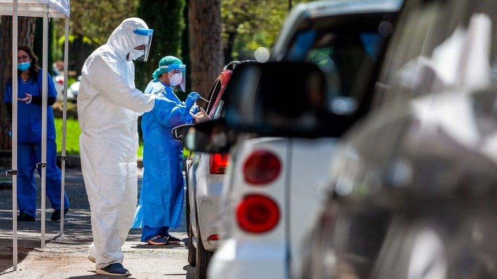Medical workers perform swabs as drivers line up at a drive-through testing facility for COVID-19 in Rome