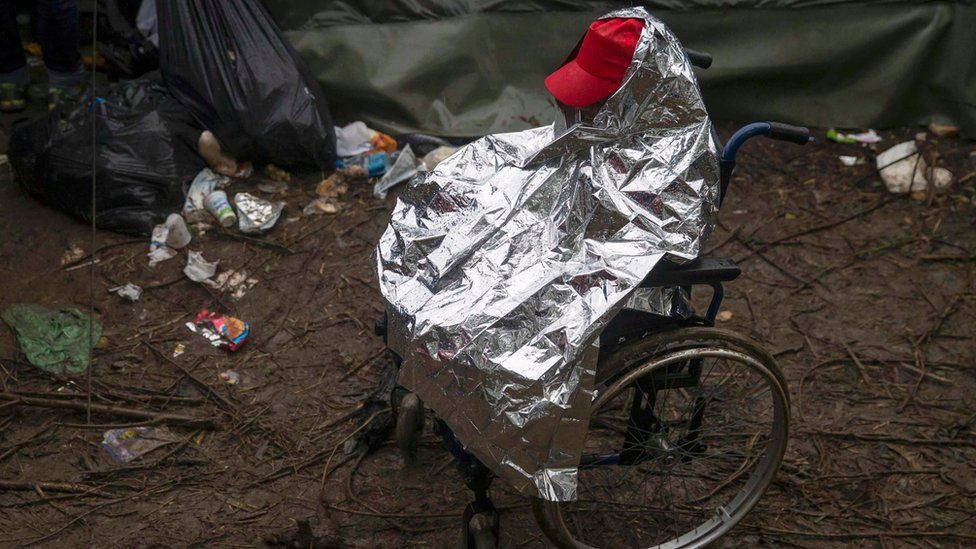 A migrant on a wheelchair protects himself from the rain near the border crossing with Croatia, near the village of Berkasovo, Serbia October 19, 2015.