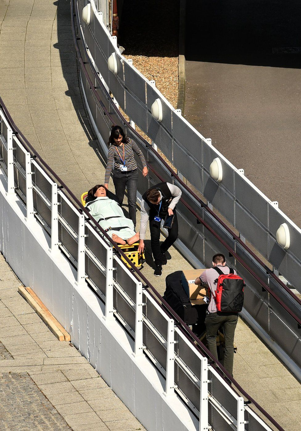 Medical staff move the dummy of a patient on a trolley