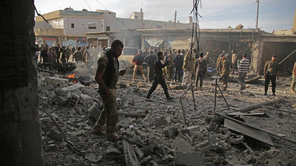 Turkey-backed Syrian fighters inspect the site of a car bomb explosion in the northern Syrian Kurdish town of Tal Abyad, on the border with Turkey, on November 2, 2019.