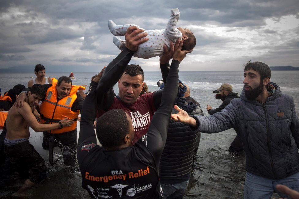 A volunteer holds up a baby as others help migrants and refugees to disembark from a dinghy on Lesbos