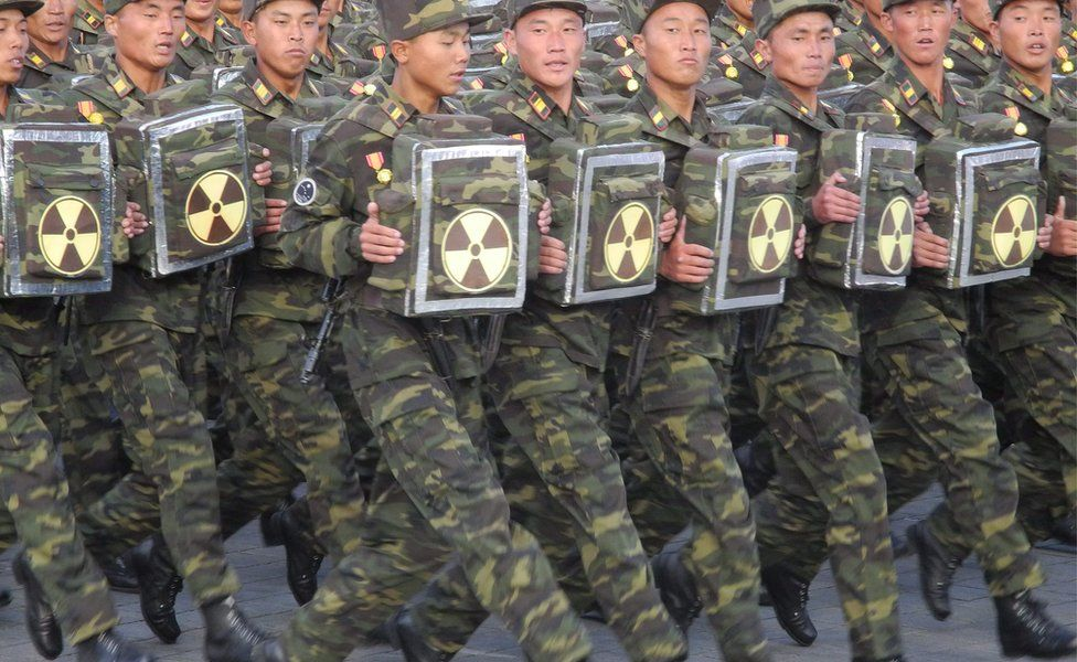 Soldiers carrying a items with the nuclear sign on them during the military parade for the 70th anniversary of the founding Workers' Party, Pyongyang, North Korea - Saturday 10 October 2015