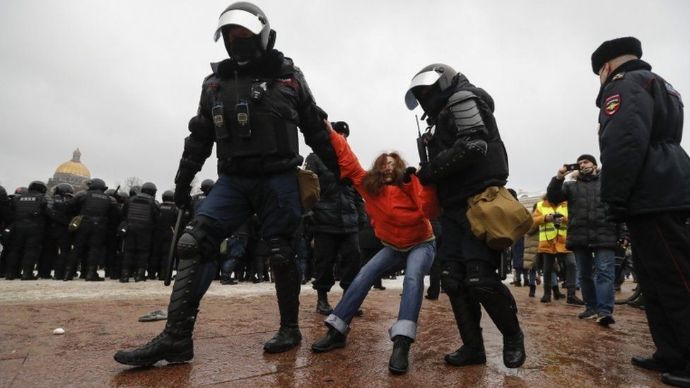 Russian special police units officers detain a female protester in St Petersburg
