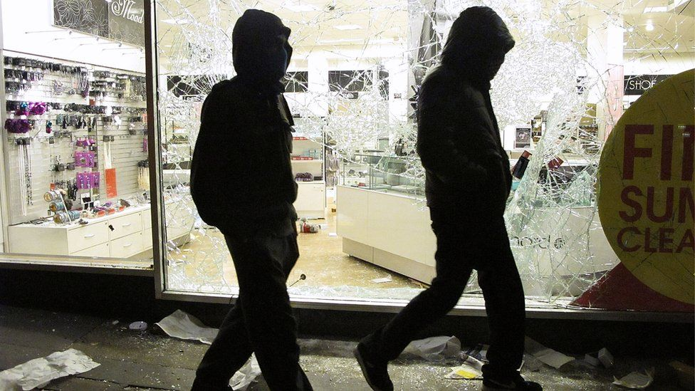 Youths walk past the looted Debenhams store in Clapham Junction, on 8 August 2011