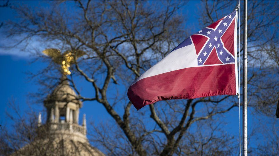 The Mississippi State Capitol dome is visible in the distance as the flag of the state of Mississippi flies