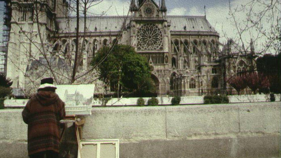 A Paris street artist paints the Notre-Dame