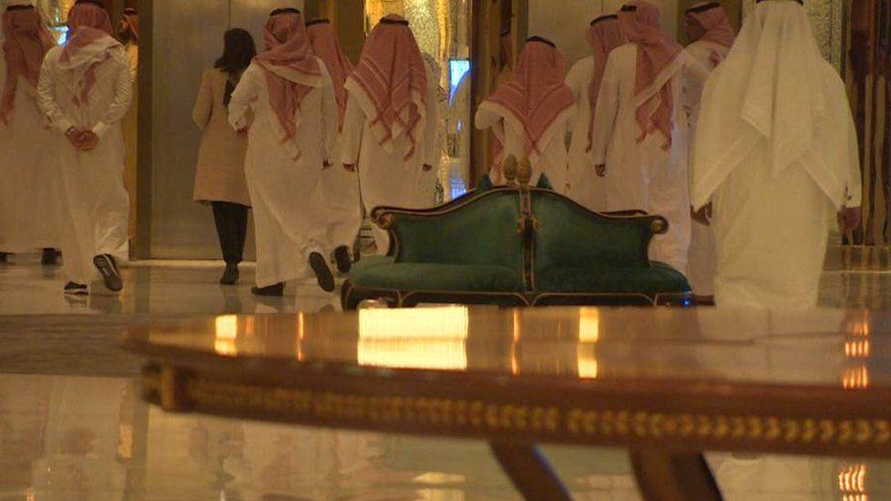 Saudi men in traditional dress are escorted through the Ritz Carlton in Riyadh.