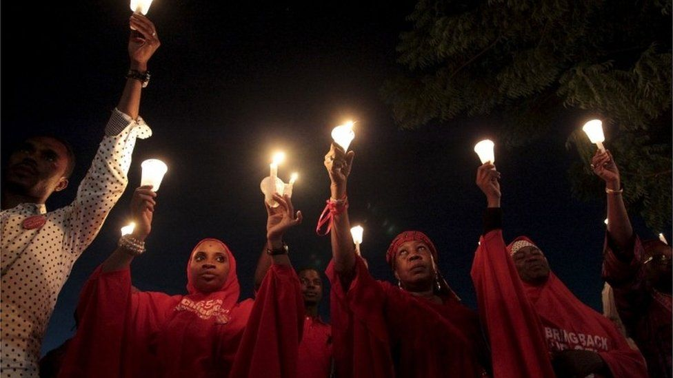Bring Back Our Girls (BBOG) campaigners raise up candles during a candle light gathering marking the 500th day since the abduction of girls in Chibok, along a road in Abuja, 27 August 2015