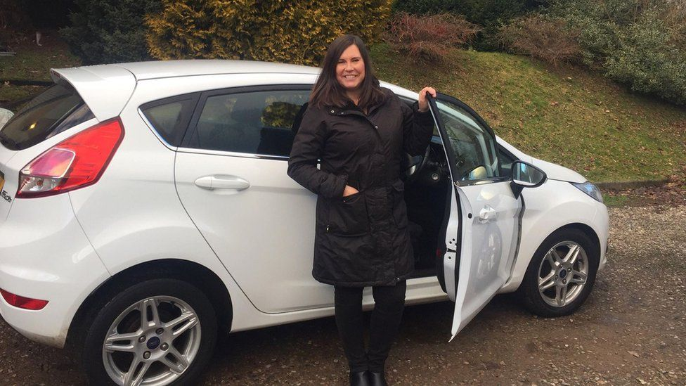 Karen Aycan standing with the car she teaches people to drive in