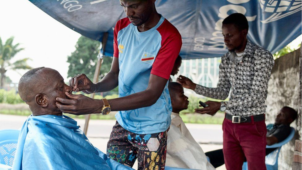 Barbers shave their clients at an open stall in the Lingwala district of the Democratic Republic of Congo's capital Kinshasa