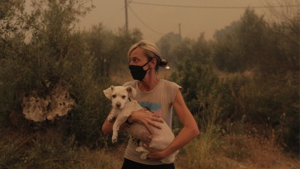 A local resident holds her dog that was rescued by locals during a wildfire