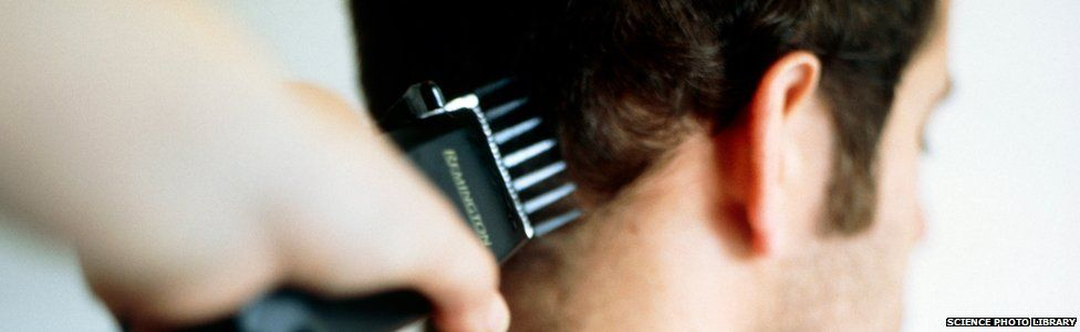 Haircut. Rear of a man's head as he has his hair cut with clippers. M985/0134