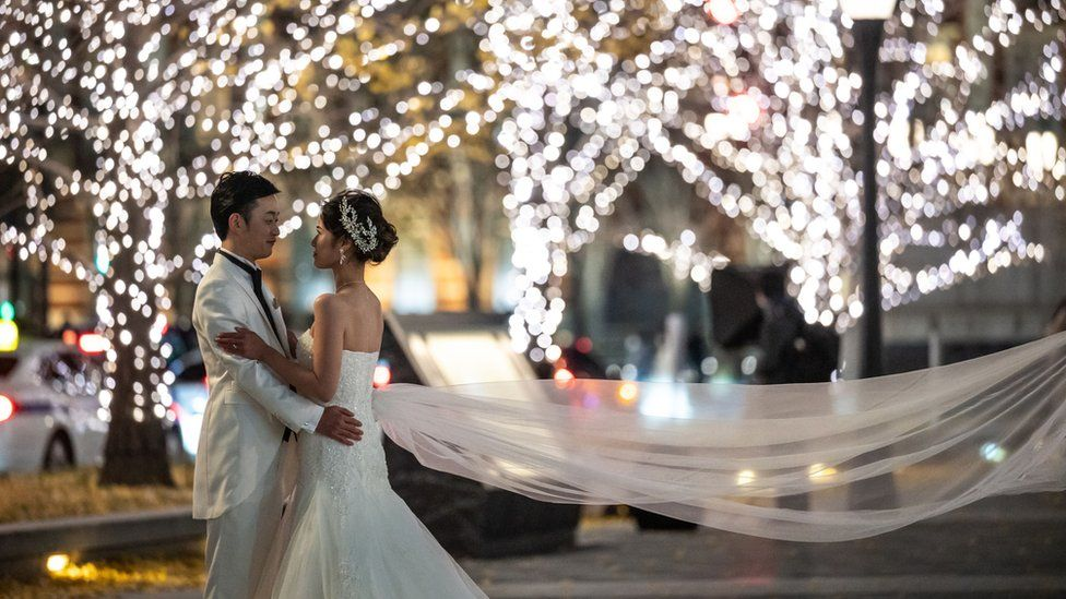 A couple pose for a wedding photo shoot in Tokyo in December 2020.