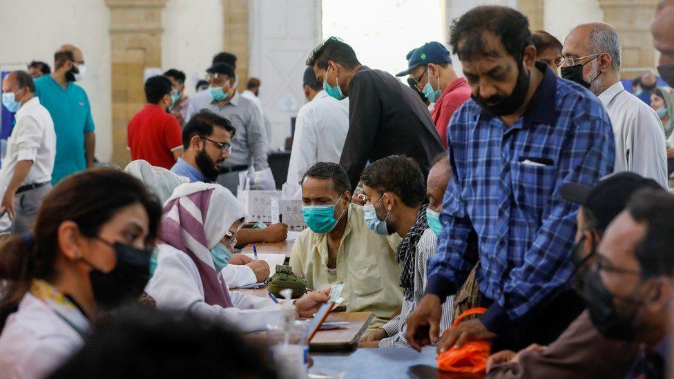 Люди собираются, чтобы получить дозы вакцины против коронавируса (COVID-19), в центре вакцинации в Карачи, Пакистан, 28 апреля 2021 г.