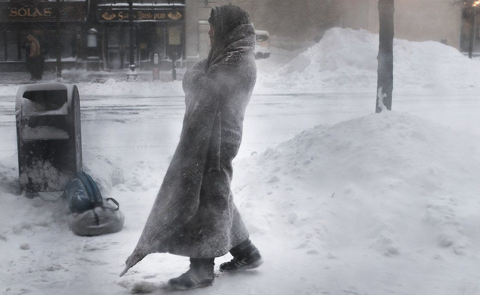 A homeless man on the streets of Boston as snow falls from a massive winter storm, 4 January 2018