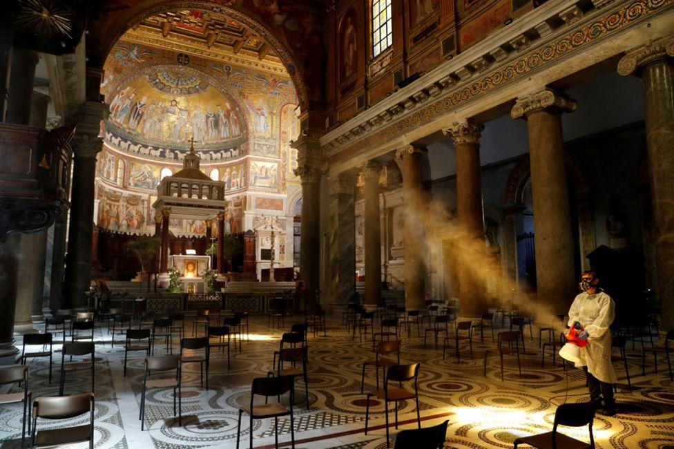 A man disinfects Rome's Basilica di Santa Maria in Trastevere