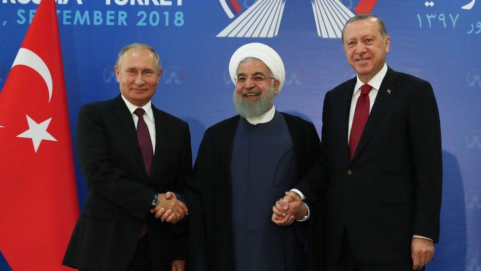 Vladimir Putin, Hassan Rouhani and Recep Tayyip Erdogan shake hands at a summit in Tehran, Iran (7 September 2018)