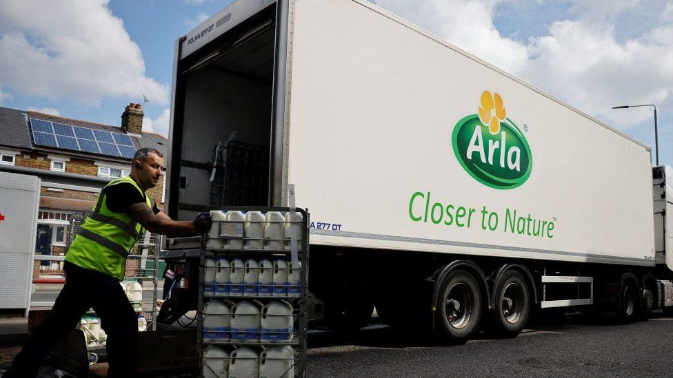 A man delivers milk next to an Arla lorry
