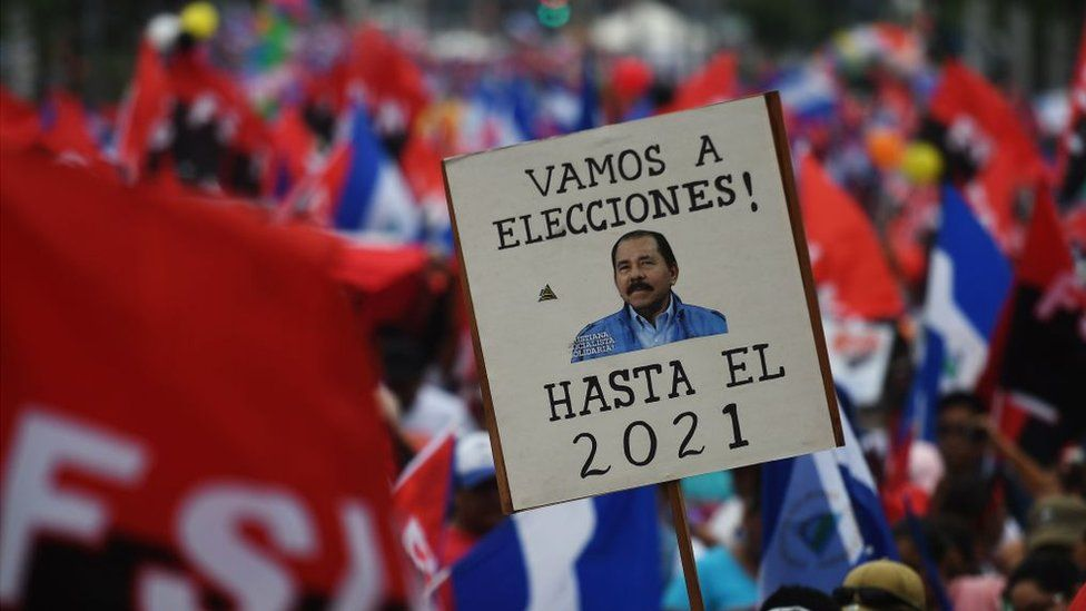 "A supporter of Nicaraguan President Daniel Ortega holds a placard reading ""Let's go to the Polls. [Ortega] Until 2021"" at protest in Managua on 7 July 2018"